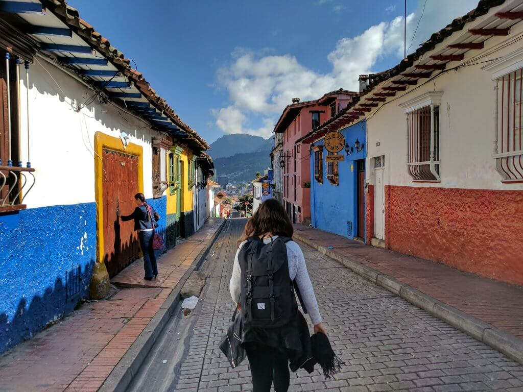 woman walking through colorful town in South America