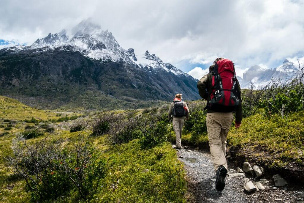 photo from behind of two hikers with mountains in the background