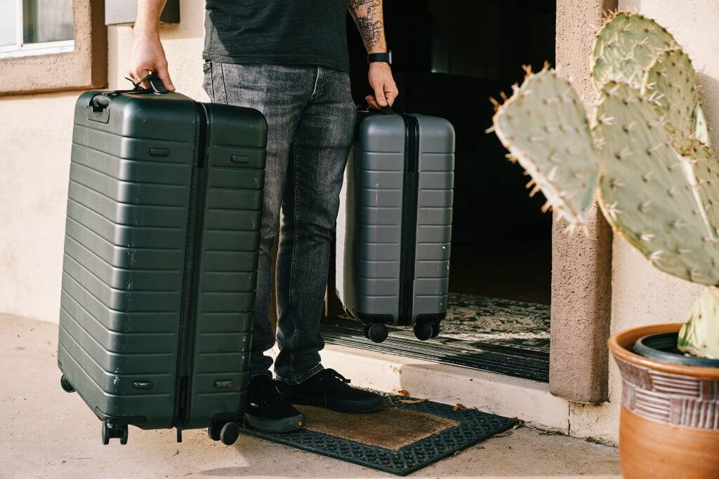 waist down photo of a man holding two suitcases outside of his front door