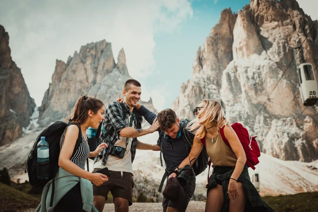 friends laughing while traveling and wearing backpacks