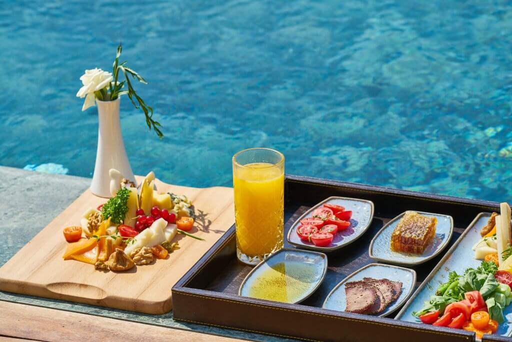 Colorful platter of brunch foods next to a hotel pool