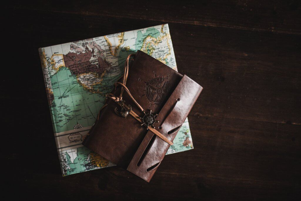 leather travel journal placed over folded map