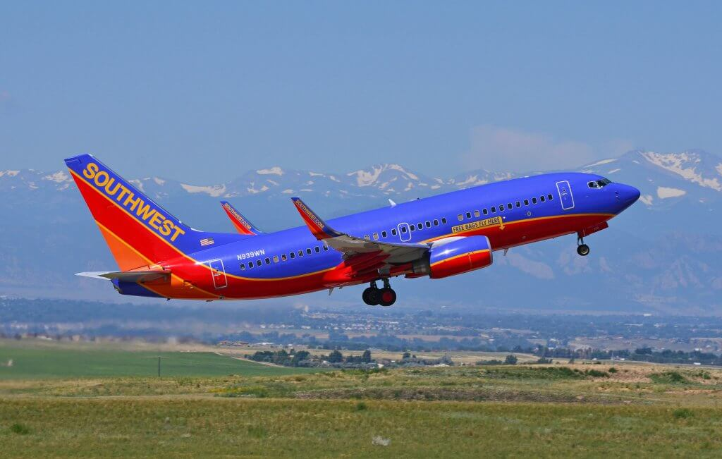 Southwest Airlines plane taking off with Denver mountains in the background