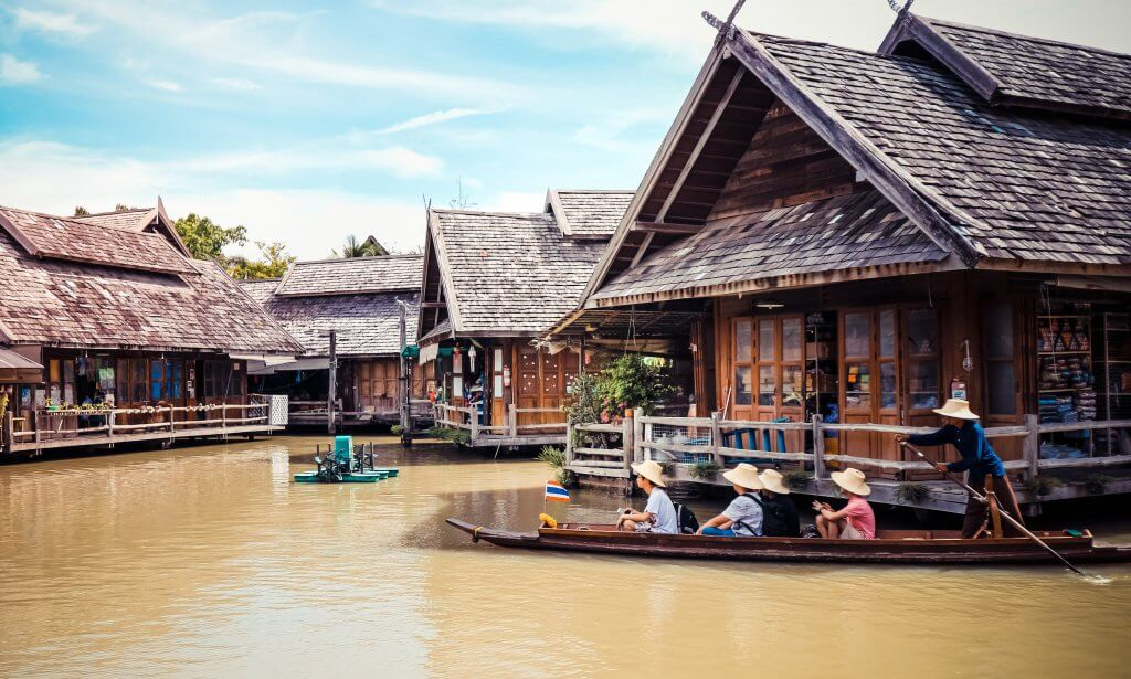Group of people on a boat tour at a floating market in Thailand