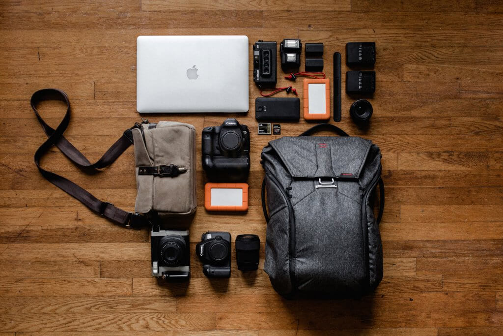 flat lay of a laptop, cameras, hard drives, and a backpack