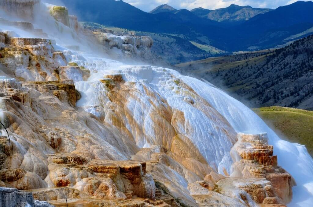 Mammoth hot springs in yellowstone national park with trees and rolling hills in the background