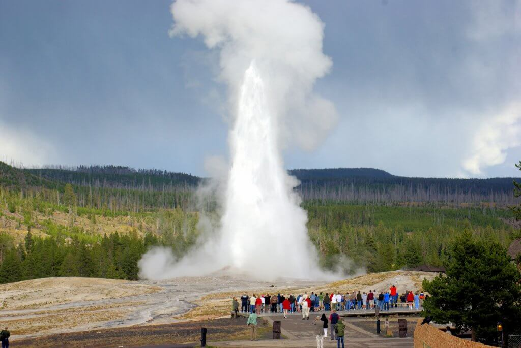 people gathering on a boardwalk as Old Faithful Geyser erupts in yellowstone national park