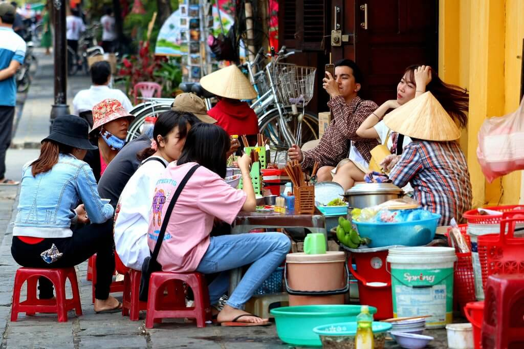 women sitting on a sidewalk while eating in Hanoi Vietnam