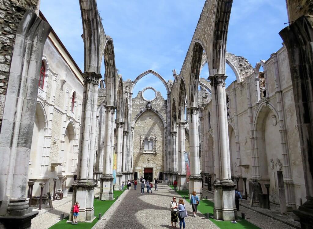 tourists walking through the stone ruins of the carmo convent in lisbon portugal