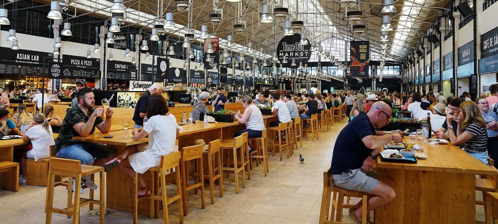 people seated at tables inside of the crowded time out food market