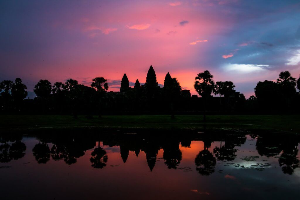 Pink sky sunrise behind Angkor Wat temple complex in Siem Reap, Cambodia