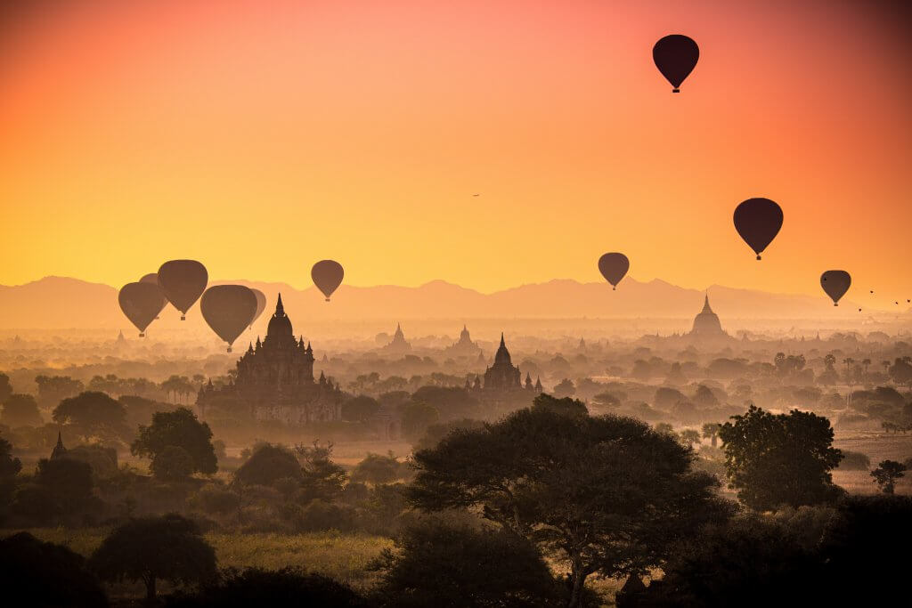 silhouettes of hot air balloons flying over temples in Bagan, Myanmar