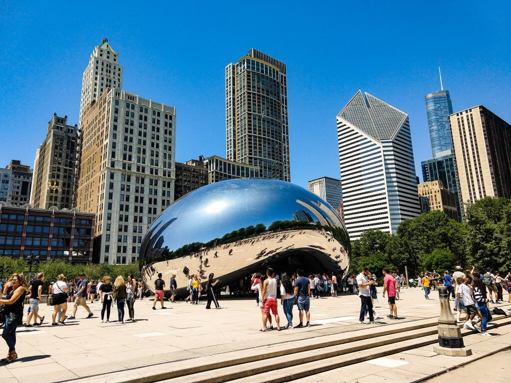 tourists crowd around and take selfies at the bean AKA cloud gate