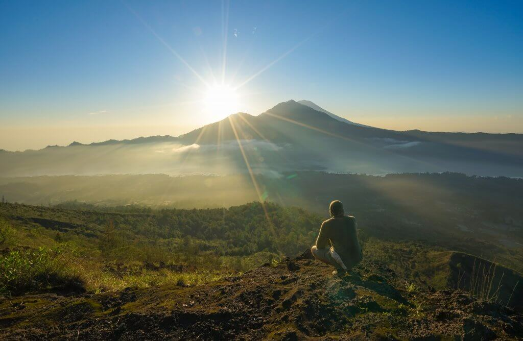 man watching the sun come up behind mountain in Bali