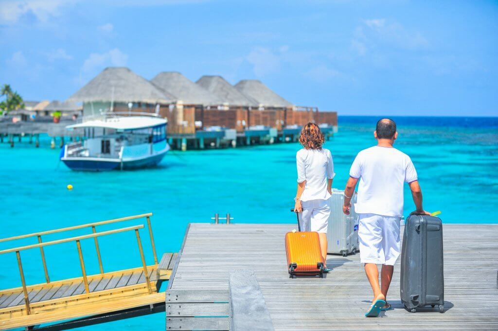 couple on a romantic getaway pulling suitcases toward over water bungalows