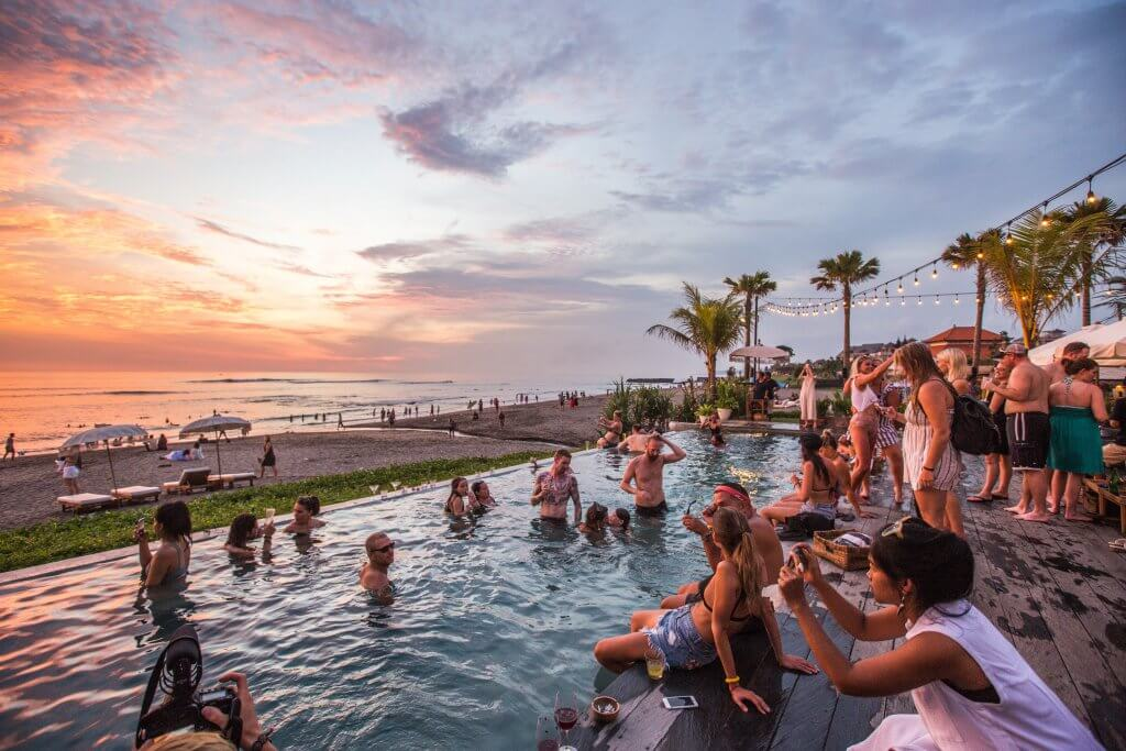 people in a beachside pool s the sunsets in canggu bali