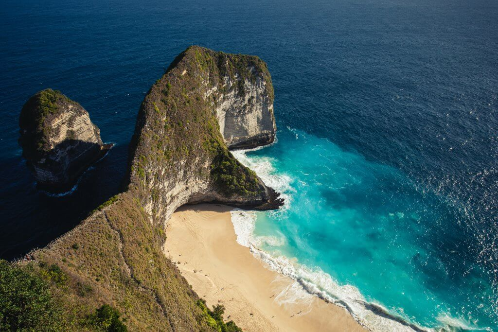 aerial view of a shoreline rock form that resembles the open mouth of a Dinosaur on Nusa Penida, Bali