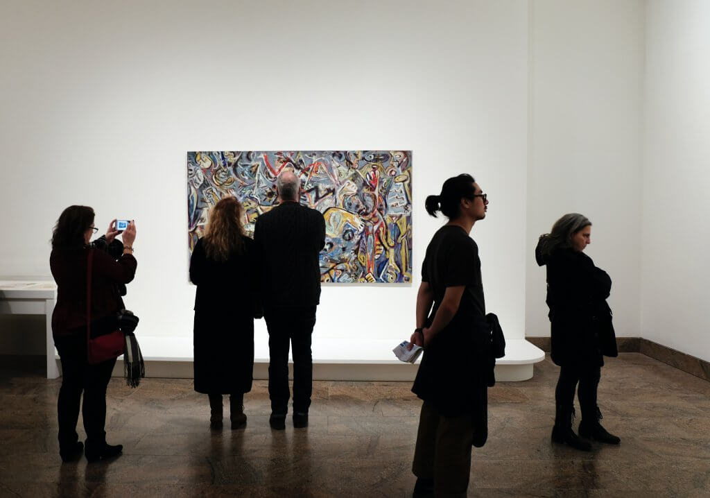 people in an art gallery with white walls and one colorful painting