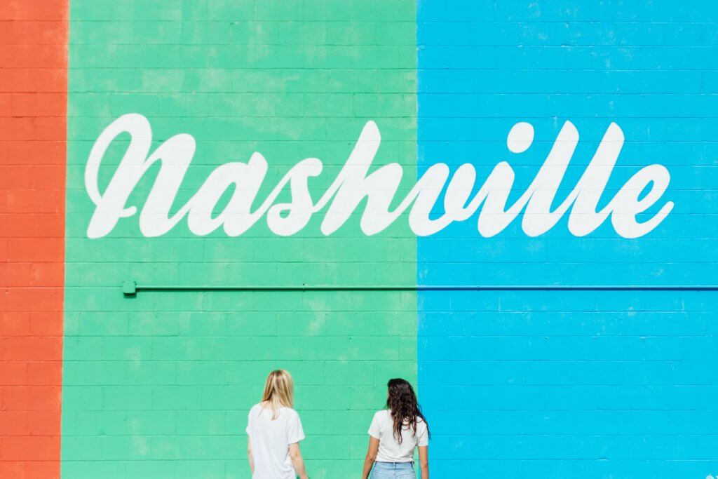 """two women stand with their backs to the camera facing a mural that says """"nashville"""""""