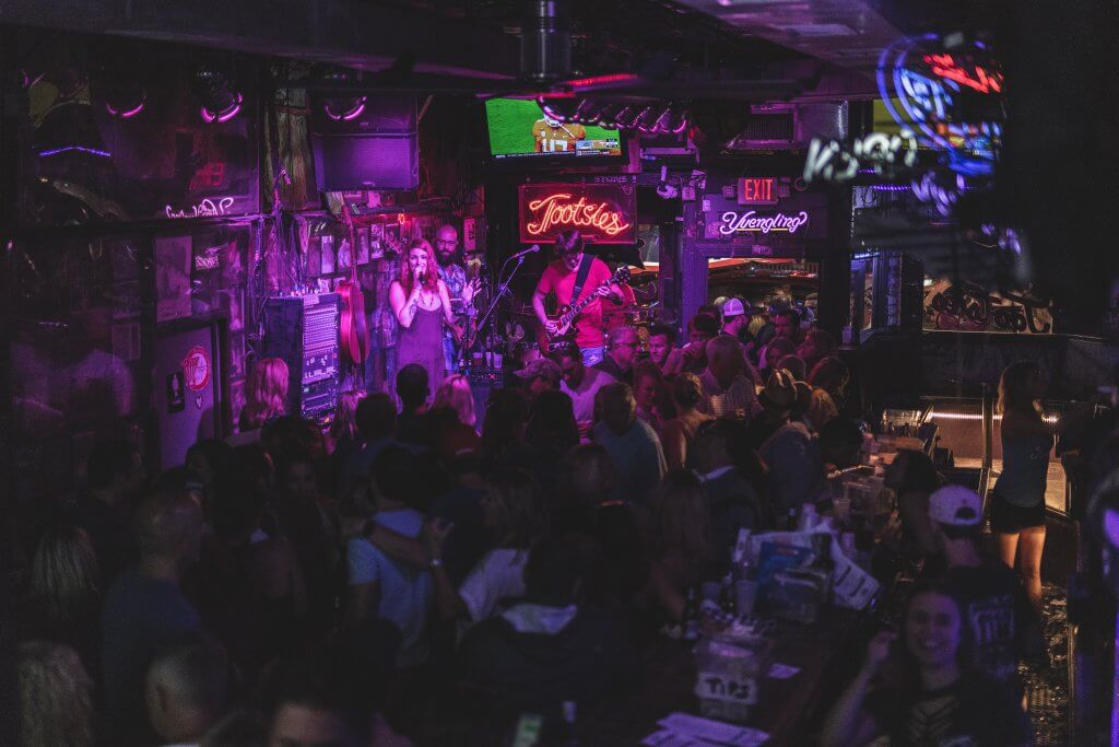 band plays in a dark neon lit room at Tootsie's Orchid Lounge