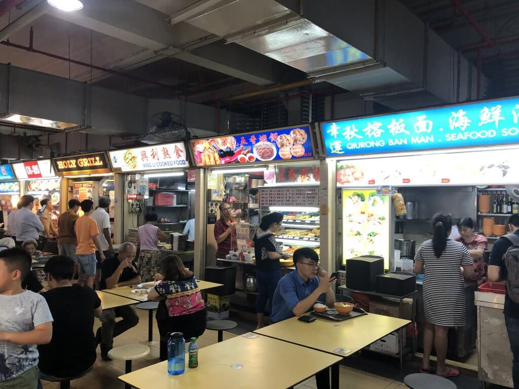 people sit in front of food stalls at Singapore's old airport road hawker center