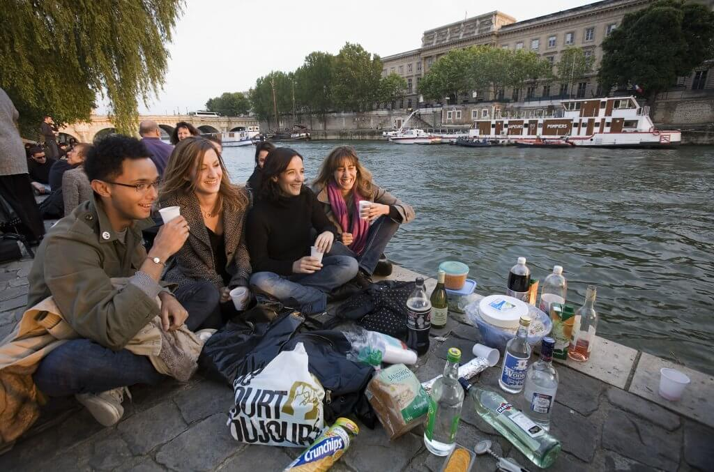 travelers having a picnic on the Seine River banks in Paris, France