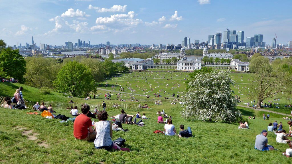 People enjoying a picnic in Greenwich park looking at the London skyline