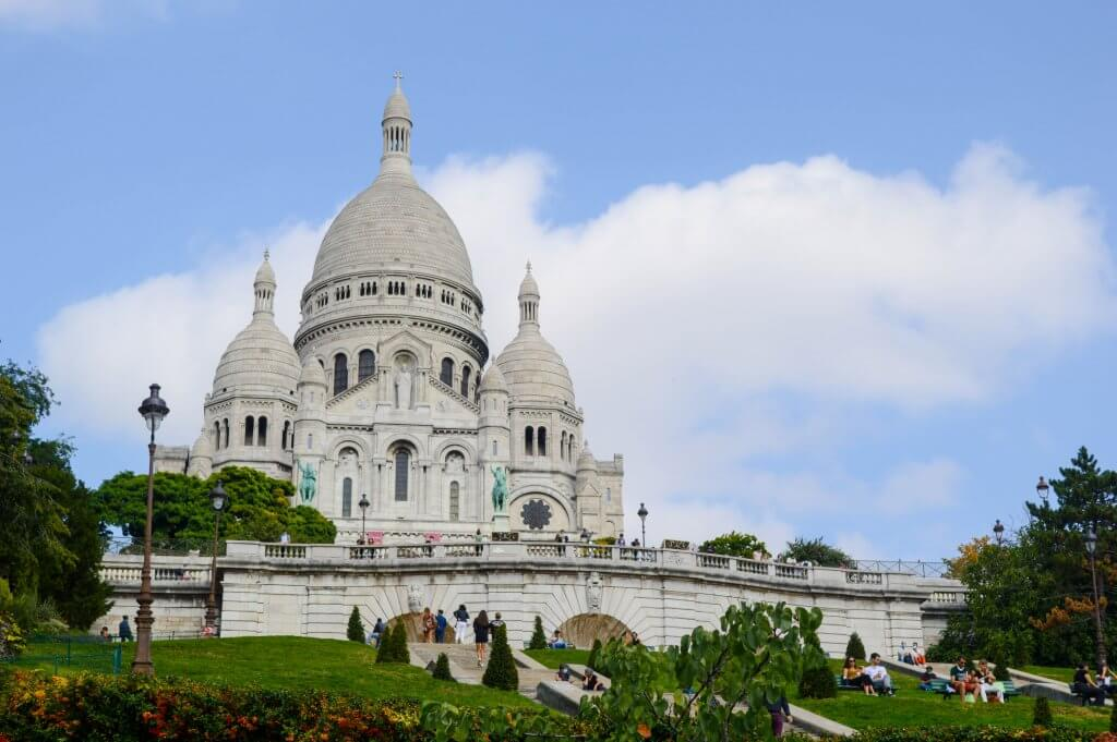 exterior front view of Sacré Coeur, a white basilica in paris, france