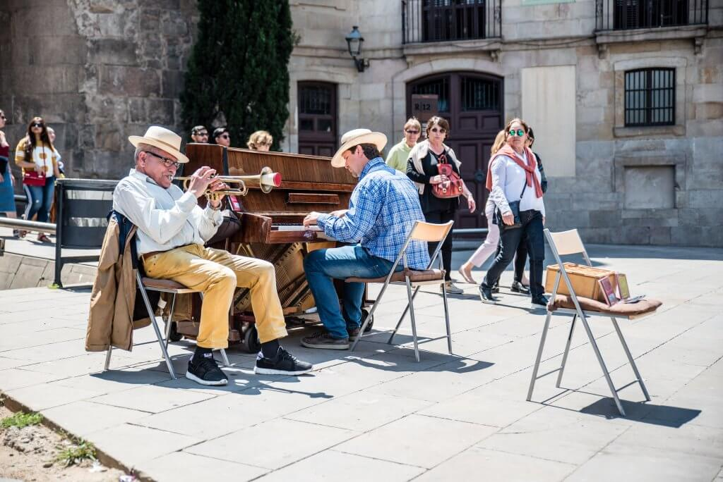 men play the piano and trumpet in the gothic quarter of Barcelona