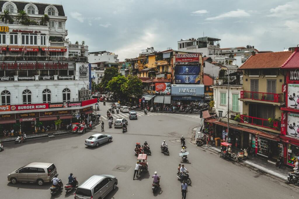 motorbikes and cars drive through a hanoi intersection