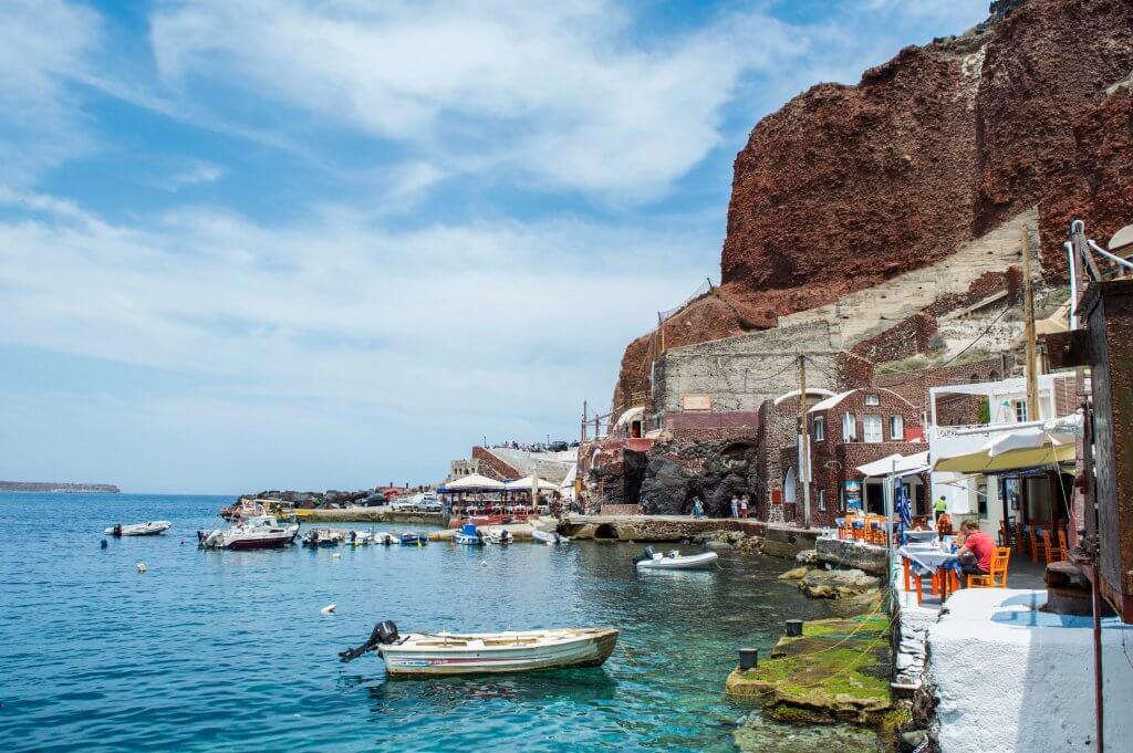 Restaurants and boats docked along Amoudi Bay in Santorini