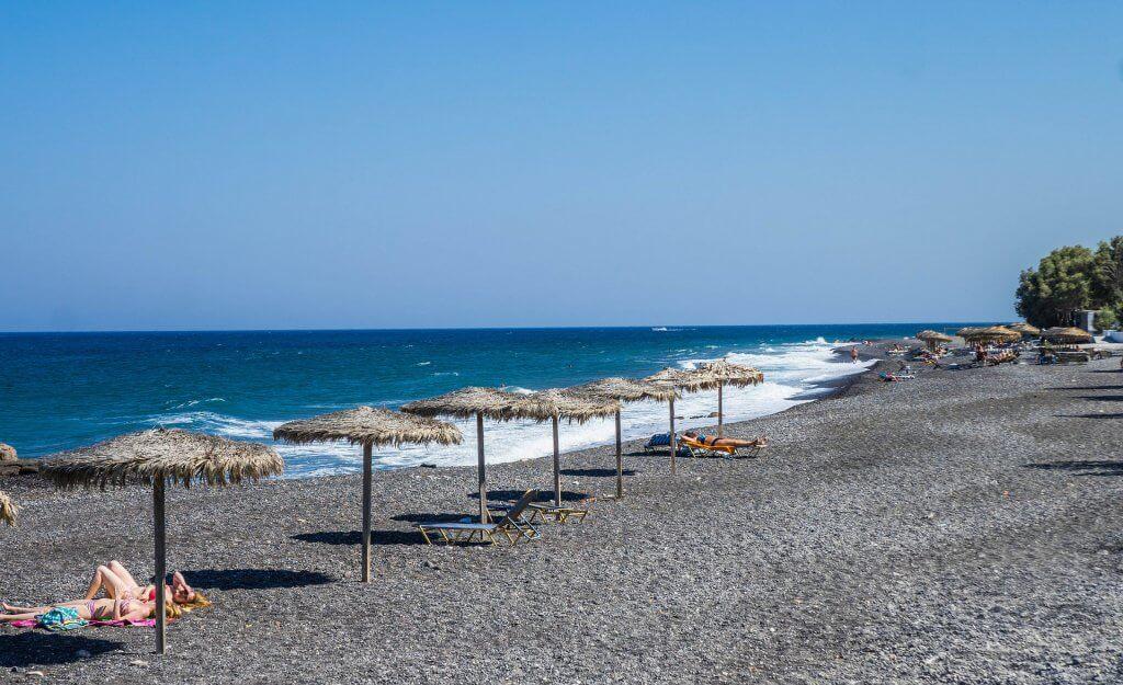 shoreline view of umbrellas along kamari beach in santorini greece