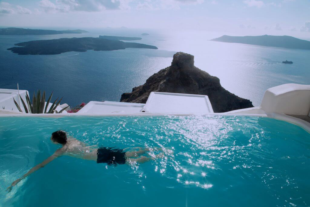 man swimming in a pool with an ocean view in santorini