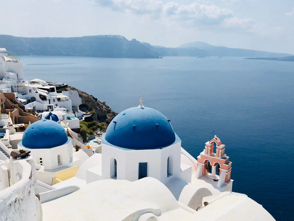 blue domed homes of oia with ocean in the background