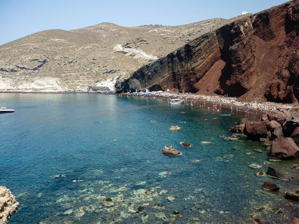 view of sunbathers on Santorini's red beach from above
