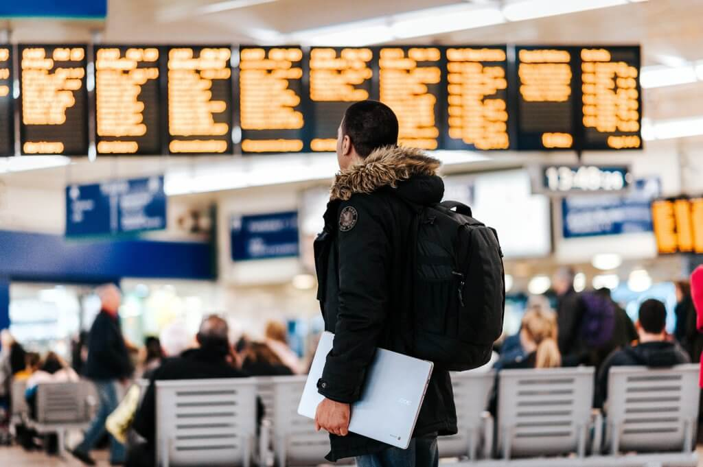 man holding laptop in an airport while looking at the flight departure board