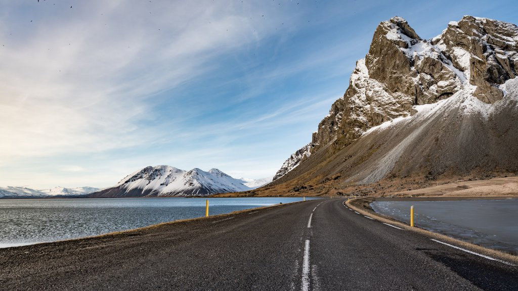 road flanked by water on both sides with a mountain up ahead