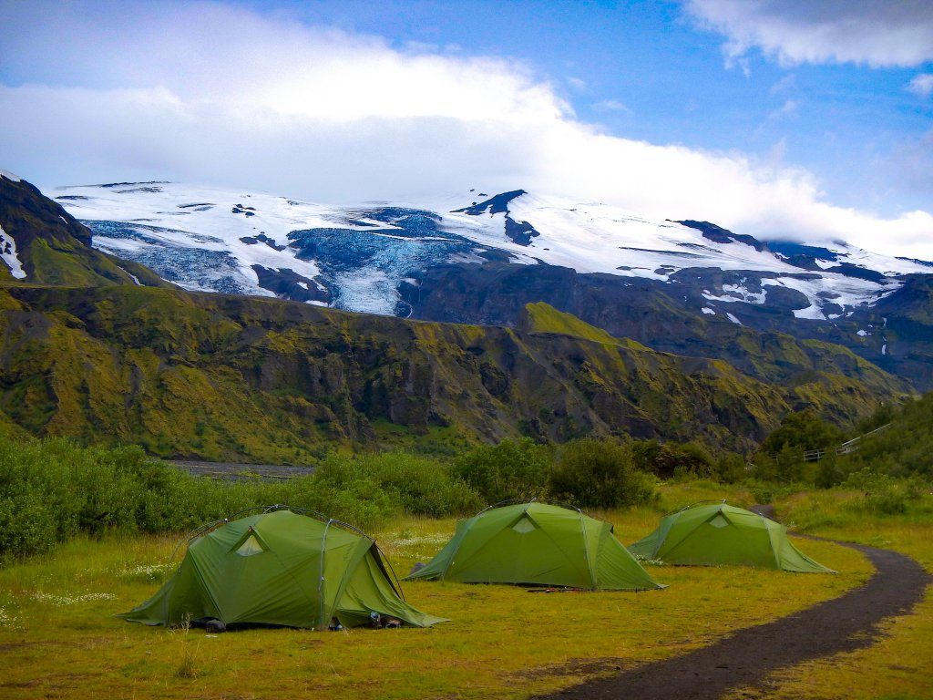 green camping tents against a mountain backdrop