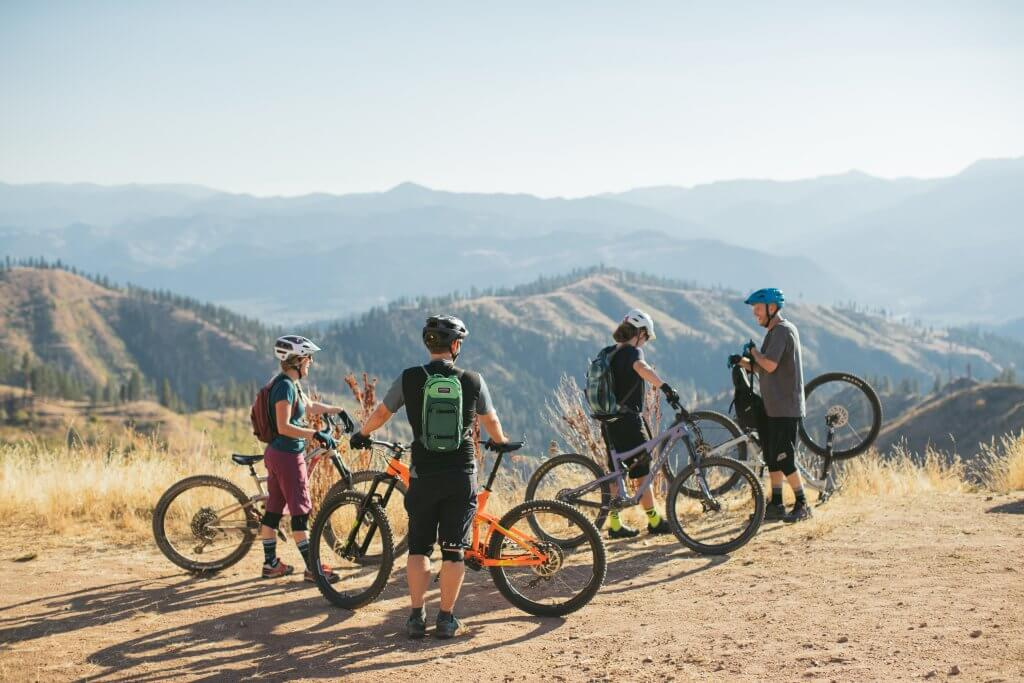 group of friends on a bike ride stop to converse at an overlook