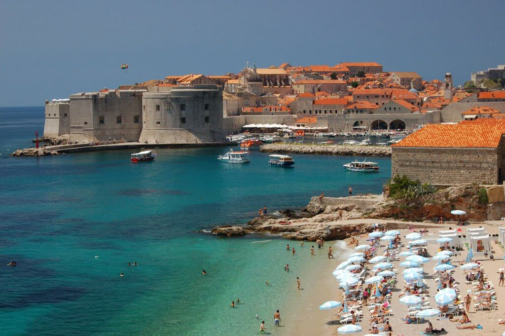 People enjoying the beach in Dubrovnik with the city in the background