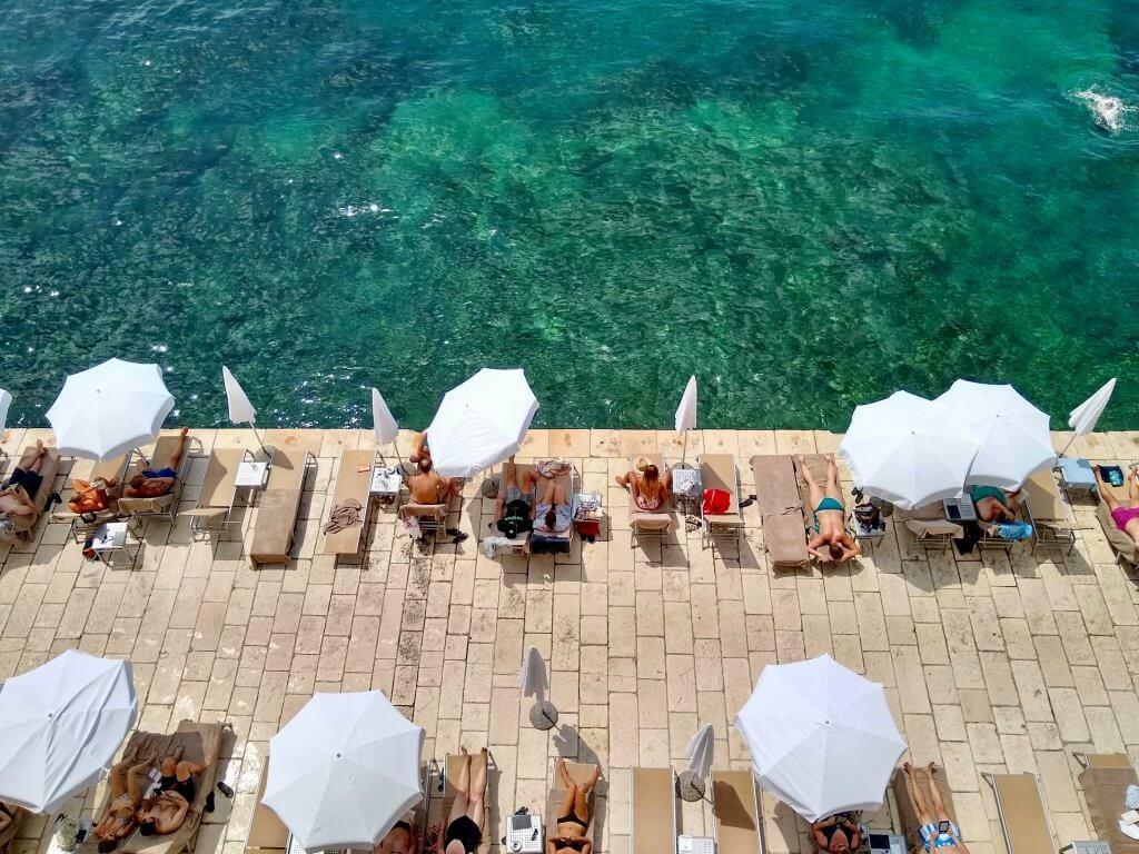 aerial shot of sunbathers underneath umbrellas in Croatia