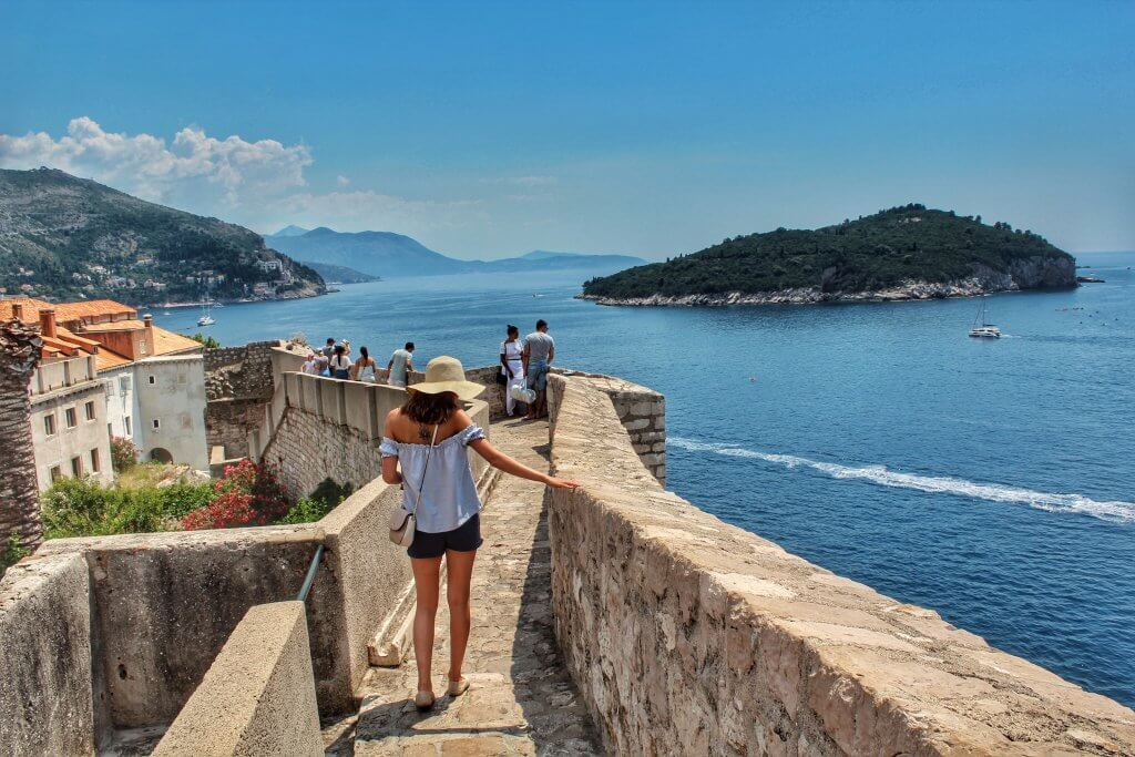woman walking along Dubrovnik's old city walls while looking out over the sea