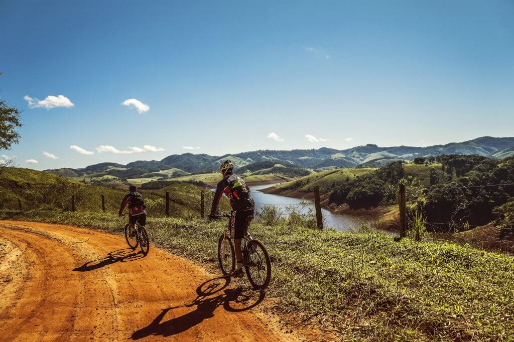 photo from behind of two people riding bicycles on a dirt road