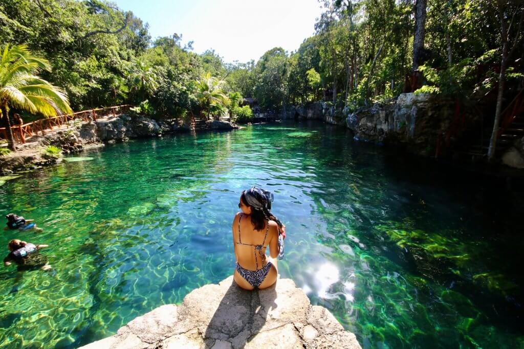 woman sits on a rock overlooking a cenote near Tulum, Mexico