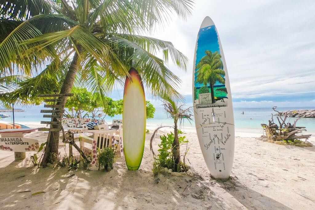 surf boards on a beach advertising prices for rentals in Maafushi, Maldives