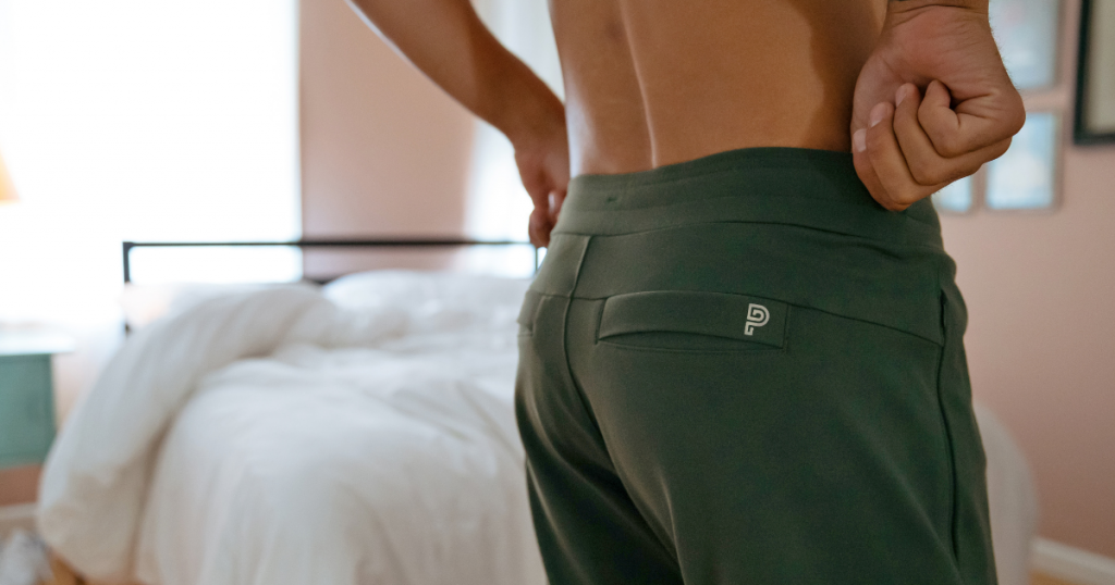 from behind shot of man putting on public rec all day every day pants
